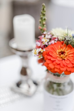 Tischdeko mit bunten Wiesenblumen bei Hochzeit in den Bergen im Bayerischen Wald mit Almhütte als Hochzeitslocation fotografiert von Hochzeitsfotografin veronika anna fotografie aus straubing