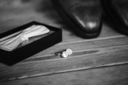 Einblick in das getting ready mit Anzugschuhe und Gürtel und Fliege und Manschettenknöpfe für den Hochzeitsanzug von Bräutigam Tom fotografiert von Hochzeitsfotograf veronika anna fotografie aus München
