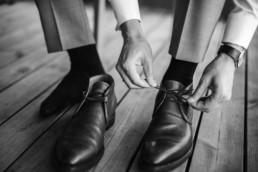 Bräutigam Tom zieht im Hochzeitsanzug seine Anzugschuhe am Hochzeitstag beim getting ready an und wird fotografiert von Hochzeitsfotograf veronika anna fotografie aus München