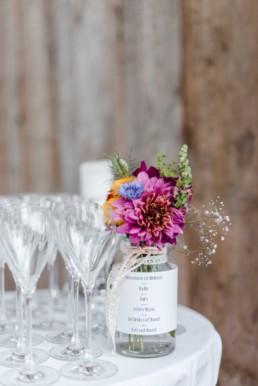 Hochzeitsdeko mit Wiesenstrauss und Blumenschmuck bei der Berghochzeit im Bayerischen Wald mit freier Trauung auf einer Bergwiese fotografiert von Hochzeitsfotografin veronika anna fotografie aus straubing