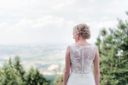 Braut Julia im weißen Brautkleid mit Spitze beim getting ready für die freie Trauung auf einer Wiese in den Bergen im Bayerischen Wald fotografiert von Hochzeitsfotografin veronika anna fotografie aus straubing
