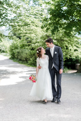 Marie und Leon wie sie für ihr Hochzeitsfoto von Hochzeitsfotograf Veronika Anna Fotografie in Tegernsee entlang spazieren