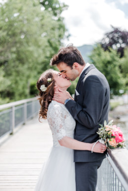 Hochzeitsfoto von Veronika Anna Fotografie wie sich Leon und Marie auf einem Steg in Oberbayern küssen