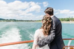 Hochzeitsfoto von Leon und Marie wie sie Arm in Arm von einem Schiff aus auf das Ufer vom Tegernseer blicken