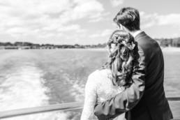 Brautpaar von hinten auf Schiff wie sie zum Ufer vom Tegernsee blicken