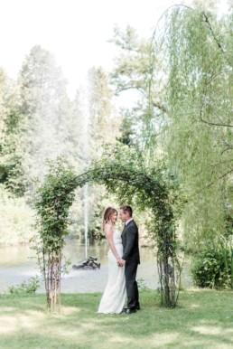 Gregor und Lena wie sie beim Fotoshooting mit Veronika Anna Fotografie unter einem Blumenbogen vor einem Teich in München stehen