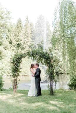Gregor und Lena unter einem Blumenbogen im Garten von München