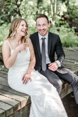 Gregor und Lena lachend auf Steg sitzend in der Natur von München