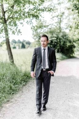 Hochzeitsfotograf Veronika Anna Fotografie hält fest wie Gregor einen Waldweg bei München entlang läuft