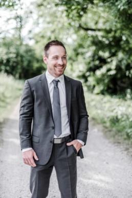 Fotoaufnahme von Gregor im Anzug auf einem Waldweg in Oberbayern