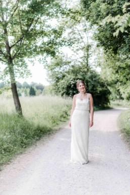 Lena wie sie beim Fotoshootings mit Hochzeitsfotograf Veronika Anna Fotografie aus Straubing einen Waldweg entlang läuft