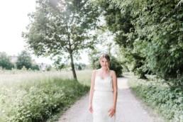 Lena im Brautkleid auf einem Waldweg in Oberbayern