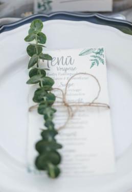 Fotoaufnahme durch Hochzeitsfotograf Veronika Anna Fotograf von Menükarte wie sie auf Teller bei der Hochzeit von Olivia und David liegt