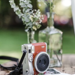 Polaroidkamera auf einem Tisch draußen bei der natürlichen Hochzeit von Olivia und David in Oberbayern