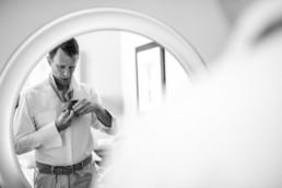 Bräutigam Daniel bindet seine Krawatte beim getting ready am Hochzeitstag in Schweden fotografiert von Hochzeitsfotograf Veronika Anna Fotografie aus München