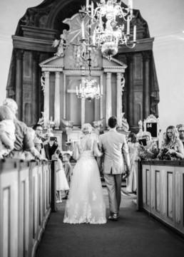 Brautpaar Petra und Daniel beim Einzug in die Kirche zu ihrer Trauung mit Hochzeitsgästen am Hochzeitstag in Schweden fotografiert von Hochzeitsfotograf Veronika Anna Fotografie aus München