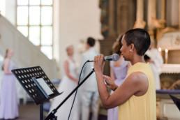 Sängerin in der Kirche am Hochzeitstag von Brautpaar Petra und Daniel bei ihrer Auslandshochzeit in Schweden fotografiert von Hochzeitsfotograf Veronika Anna Fotografie aus München