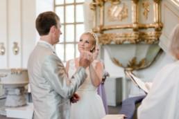 Brautpaar Petra und Daniel blicken sich verliebt an bei ihrer Trauung in der Kirche in Schweden fotografiert von Hochzeitsfotograf Veronika Anna Fotografie aus München