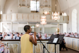 Sängerin singt in der Kirche bei der Trauung von Brautpaar Petra und Daniel bei ihrer Hochzeit in der Kirche in Schweden fotografiert von Hochzeitsfotograf Veronika Anna Fotografie aus München