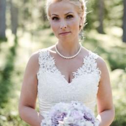 Braut Petra im weißen Hochzeitskleid mit Brautstrauß mit rosa Rosen am Hochzeitstag im Wald in Schweden fotografiert von Hochzeitsfotograf Veronika Anna Fotografie aus München
