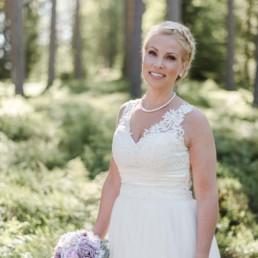 Braut Petra lacht glücklich im weißen Hochzeitskleid mit Brautstrauß mit rosa Rosen am Hochzeitstag im Wald in Schweden fotografiert von Hochzeitsfotograf Veronika Anna Fotografie aus München