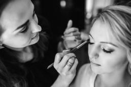 Die Braut wird am Hochzeitsmorgen geschminkt