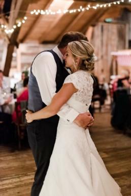 Tanzendes Brautpaar unter Lichterketten.