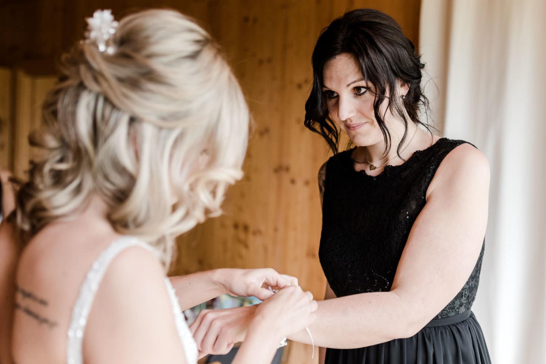 Braut legt ihrer Trauzeugin Blumen an