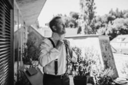 Der Bräutigam schließt sein Hemd am Hochzeitsmorgen