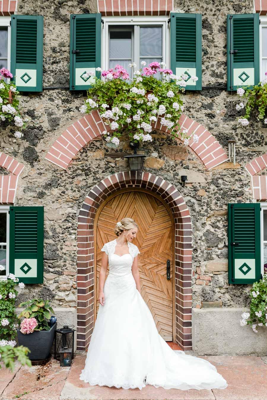 Die Braut posiert vor einer steinernen Fassade