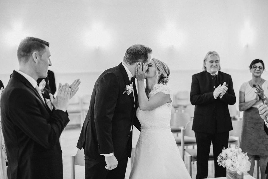 Die Braut küsst ihren Bräutigam und die Gäste applaudieren