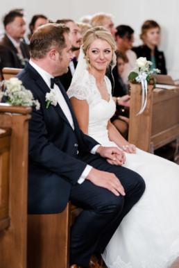 Die Braut wirft ihrem Bräutigam in der Kirche verliebte Blicke zu