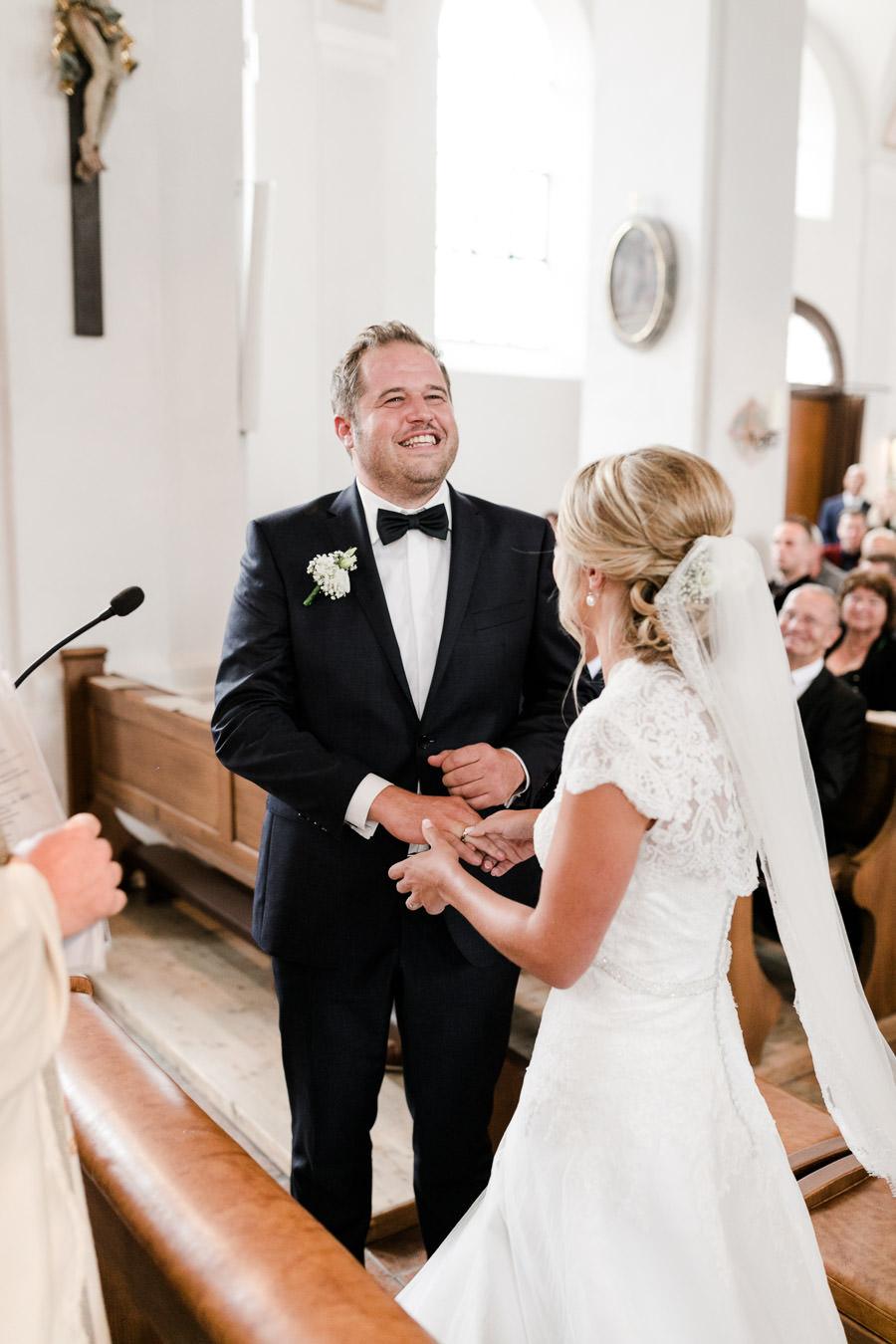 Die Braut steckt ihrem Bräutigam den Ring an.