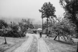 Regenhochzeit, Brautpaar unter dem Schirm bei Hochzeit am Grandsberger Hof