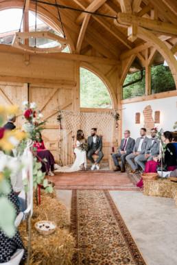 Freie Trauung in der Scheune mit Teppichen und Traubogen, Hochzeitsfotografin Veronika Anna Fotografie