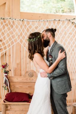 Braut und Bräutigam küssen sich vor dem Traubogen, am Grandsberger Hof, fotografiert von Hochzeitsfotografin Veronika Anna Fotografie