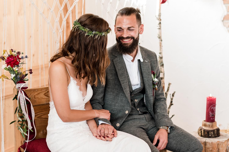 Hochzeitspaar bei freier Trauung unter Traubogen Makramee im bayerischen Wald.