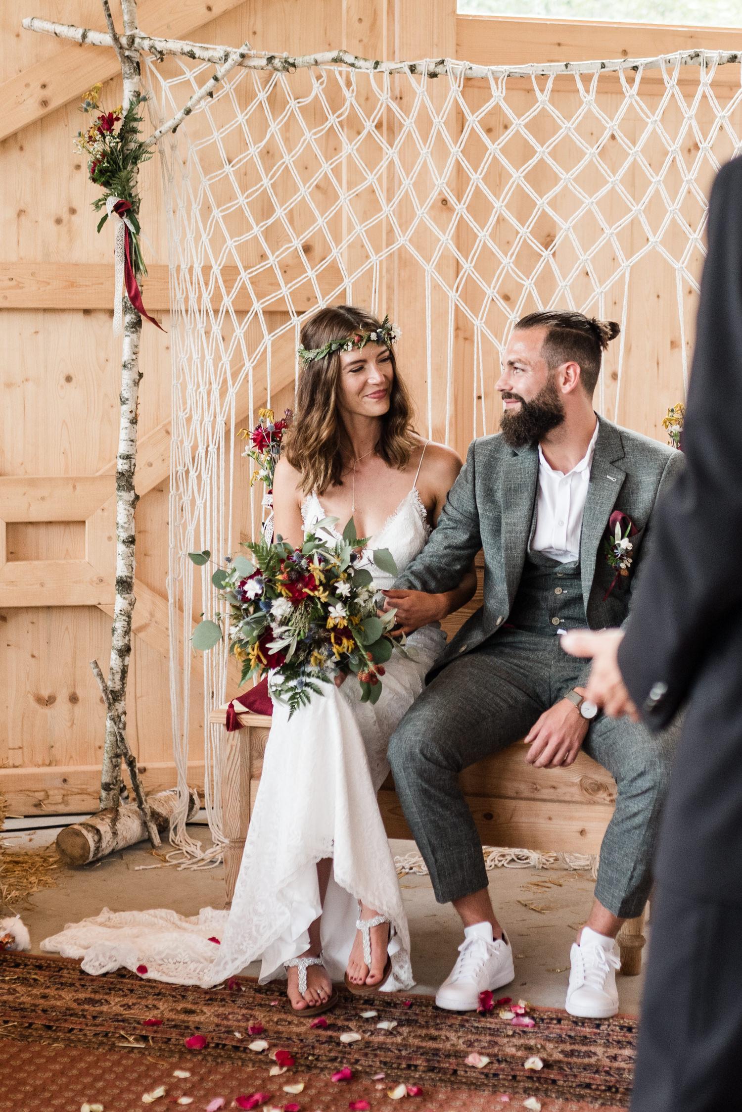 Braut und Bräutigam sitzen unter dem Traubogen im bayerischen Wald.
