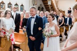 Braut betritt die Kirche mit dem Brautvater bei Trauung im bayerischen Wald, Foto von Veronika Anna Fotografie Deggendorf
