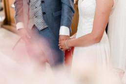 Brautpaar hält einander an den Händen, kirchliche Trauung in Deggendorf fotografiert von Veronika Anna Fotografie