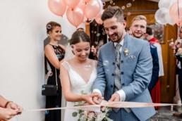 Braut und Bräutigam durchschneiden ein Band, bei Hochzeit am Wildberghof Buchet im bayerischen Wald, Foto von Veronika Anna Fotografie