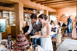 Hochzeitstorte wird angeschnitten bei Scheunenhochzeit am Wildberghof Buchet, fotografiert von Veronika Anna Fotografie ,bayerischer Wald, Deggendorf