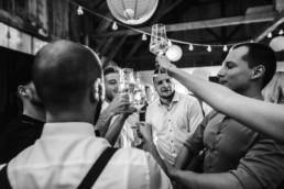 Cheers auf das Brautpaar, feiernde Gäste am Wildberghof Buchet Scheunenhochzeit von Veronika Anna Fotografie Hochzeitsfotograf Deggendorf