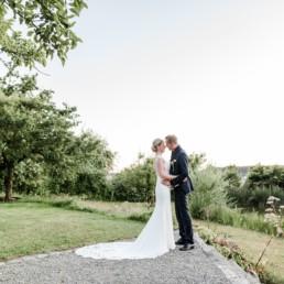 Brautpaat in verliebter Pose am Hofgut Hafnertleiten bei Gartenhochzeit im Sommer