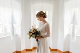 Hochzeitsfotografie von der Braut mit Brautkleid und Brautstrauß am Hochzeitstag im Schloss Maierhofen von Veronika Anna